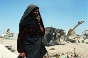 A woman stands in front of discarded military scrap in Iraq. 06/01/2003. Photo credit: Philip Reynaers/Greenpeace