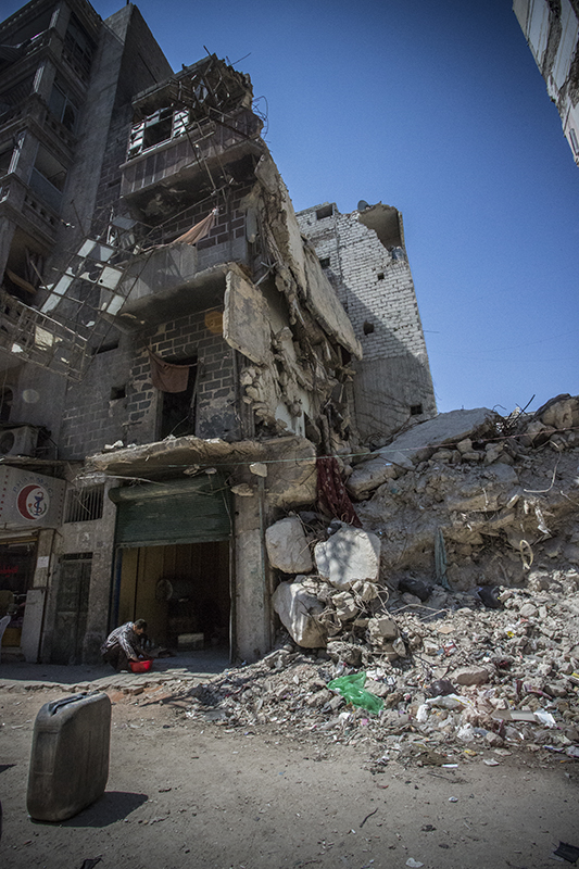 Aleppo, Syria - 2013. A building destroyed by repeated shelling, residents have tried to keep their business on the ground floor running. © Hannah Lucinda Smith