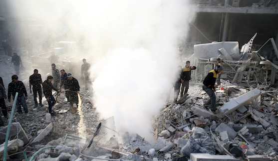 People stand on rubble of damaged buildings after an airstrike in the besieged town of Hamoria, Eastern Ghouta, in Damascus, Syria Janauary 9, 2018. REUTERS/Bassam Khabieh - RC1A03C21970