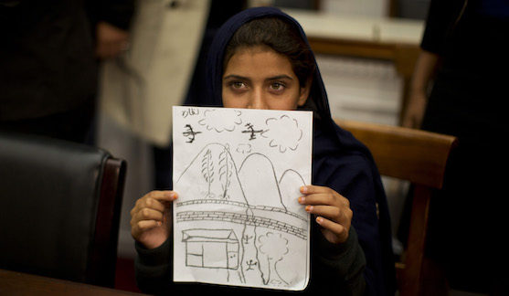 Nabila Rehman, 9, holds up a picture she drew depicting the U.S. drone strike on her Pakistan village which killed her grandmother Mammana Bibi, at a news conference on Capitol Hill in Washington October 29, 2013. Nabila and her father and brother attended the news conference on Monday to highlight the personal costs in collateral damage for civilians killed and injured in the U.S. drone strike program. REUTERS/Jason Reed (UNITED STATES - Tags: POLITICS MILITARY TPX IMAGES OF THE DAY) - GM1E9AU04C601