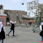 Palestinian students play basketball inside their damaged school nearby a building that was destroyed by Israeli air strikes, in Gaza City May 7, 2019. REUTERS/Mohammed Salem