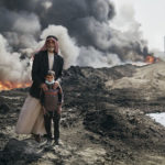 Nadak Aziz and Kharim Ali, a village elder an a young boy pose for a portrait near the Qayyarah oil fires. October 25th, 2016. Joey L./Oxfam