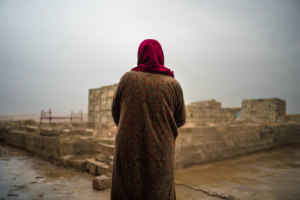 Sahala looks at the part of her family's house that was destroyed when their village was occupied by ISIS. Returning to Tulaband, Iraq, after explosives were cleared and schools were restored, the family now faces challenges to rebuilding their home and livelihood. © Emily Garthwaite/Article 36
