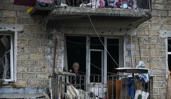 A woman looks out of her apartment window in the aftermath of recent shelling during a military conflict over the breakaway region of Nagorno-Karabakh in Stepanakert